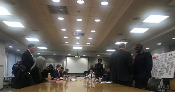 Session Attendees standing at conference table